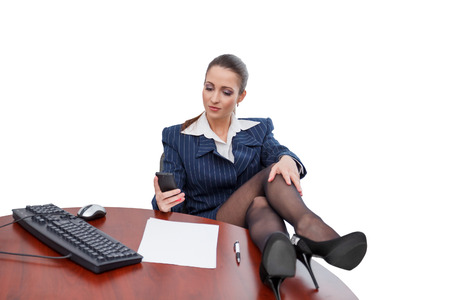 Brunette businesswoman sitting at desk with smartphone, isolated on white