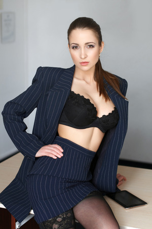 tits: Sexy young provocative teacher in underwear sitting on desk Stock Photo