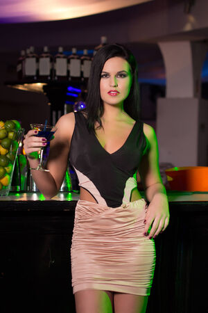 Brunette woman holding cocktail in bar at night, flirt photo