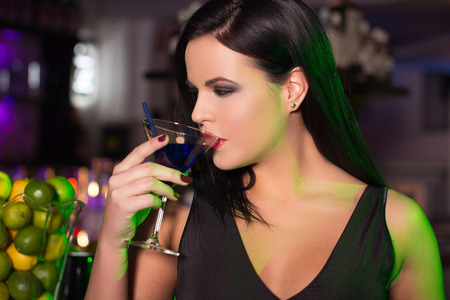 Beautiful woman drink cocktail in bar at night photo