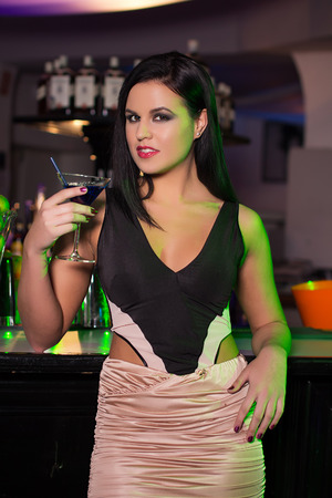 Sensual brunette woman holding cocktail in bar photo