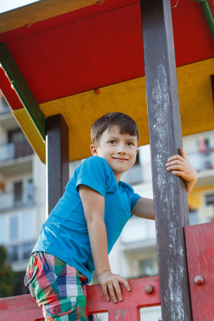 jungle gym: Little boy smile on top of jungle gym, outdoor activity Stock Photo