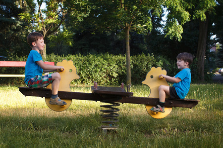 Happy little boys on seesaw in park