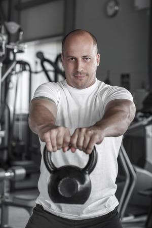 Caucasian man lifting kettlebell, training in gym photo