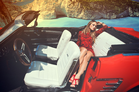 Attractive blonde woman in red cabriolet, retro style, coast background, outdoor photo