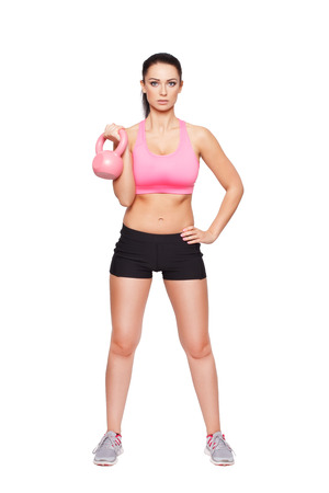 Fit woman holding kettlebell, isolated on white photo
