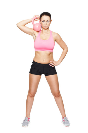 Fit woman holding kettlebell at neck, isolated on white photo