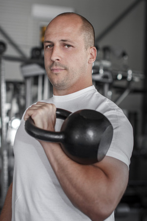 Male bodybuilder with kettlebell posing in gym photo