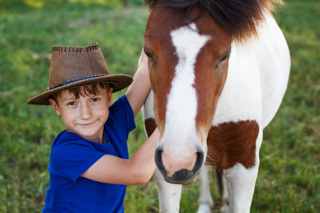 Little boy with cowboy hat and pony horse Stock Photo