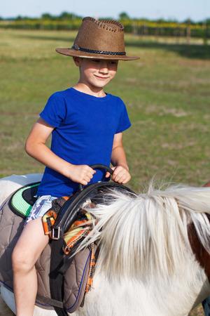 Weinig jongensrit op poney, platteland, openlucht Stockfoto