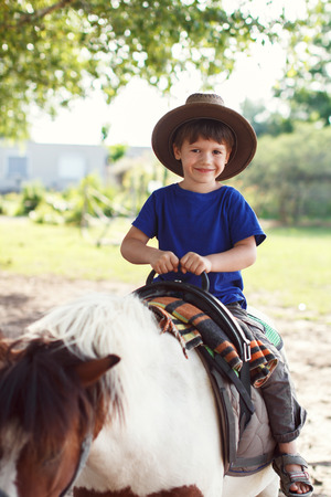 pony ride: Little kid in cowboy hat ride on pony