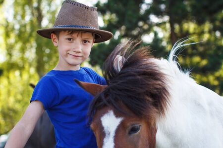 pony ride: Little boy with pony on farm, horse therapy