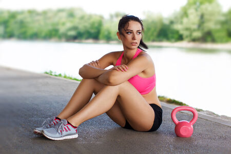 Woman sit with pink kettlebell, outdoor portrait photo