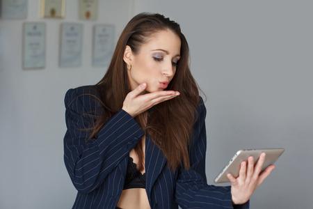 sexy naked girl: Brunette secretary in bra sending kisses, online flirt Stock Photo