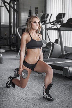 Blonde fitness model with dumbbells, lunge exercise photo