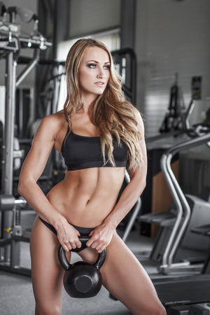 Blonde fitness model posing with kettlebell in gym photo