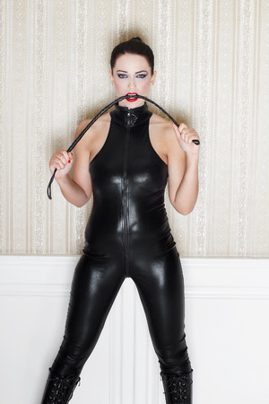domination: Sexy woman with whip in black latex catsuit, desire