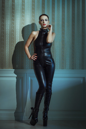 Sexy woman in latex catsuit posing at vintage wall photo