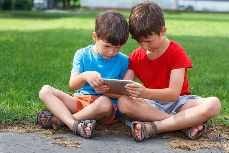 information society: Little children playing on tablet at outdoor