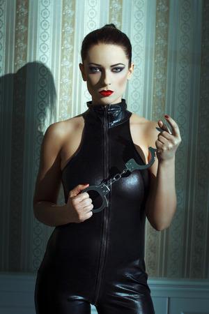 domination: Mujer atractiva en catsuit de l�tex y las esposas que presenta en la pared de la vendimia Foto de archivo