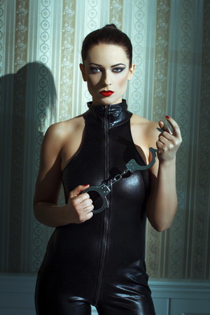 Sexy woman in latex catsuit and handcuffs posing at vintage wall photo