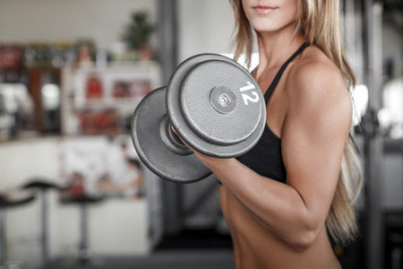dumbbell: Woman workout with dumbbell in gym, biceps exercise closeup