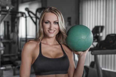 Blonde Frau mit Medizinball in der Turnhalle Standard-Bild