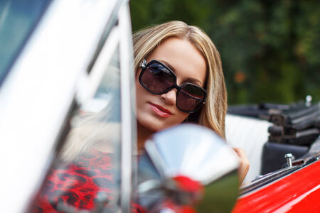 Blonde lady in red cabriolet, outdoor portrait photo