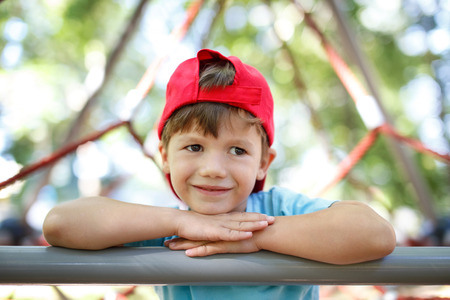 jungle gym: Little boy in cap on the jungle gym, looking away