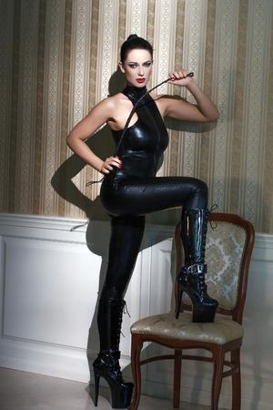 Sexy vrouw in latex catsuit met zweep stap op stoel, verlangen Stockfoto