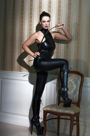 Sexy woman in latex catsuit with whip step on chair, desire