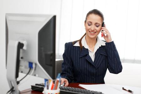 jornada de trabajo: Brunette oficinista sentado en la oficina y llamar, dientes sonríen