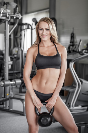 Young sporty woman holding kettlebell in gym photo