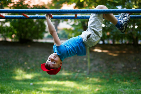 Little boy in red cap upside down at playground, outdoor activity, dangerous
