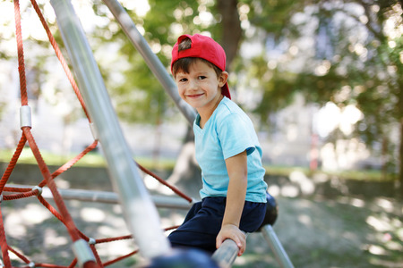 jungle gym: Little boy in cap sit on jungle gym, outdoor portrait Stock Photo