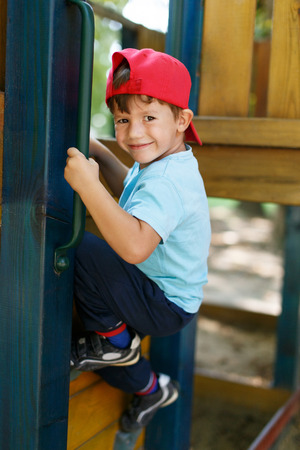 jungle gym: Little boy in cap climb up on jungle gym Stock Photo