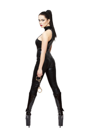 sex toys: Woman in latex catsuit and high heel platform boots holding handcuffs, bdsm, isolated on white background