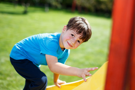 five years old: Little boy climb up on slide reverse way, bad Stock Photo