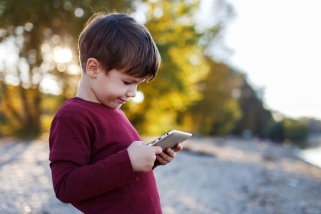 parental control: Little boy playing on tablet, outdoor portrait