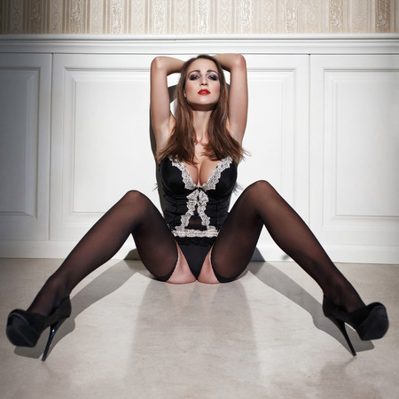 big boobs: Mujer morena sensual en cors� y medias en la noche sentarse en el piso, posando