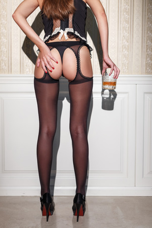 sex women: Sexy woman in black underwear holding glass of whiskey at vintage wall