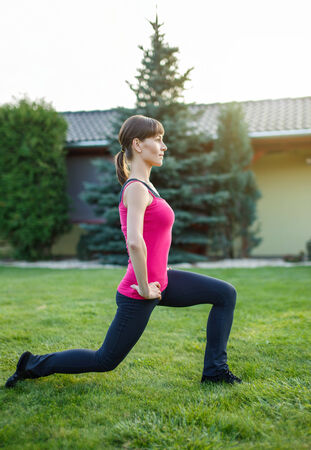 lunges: Sporty woman doing lunge exercise in sunset, outdoor portrait