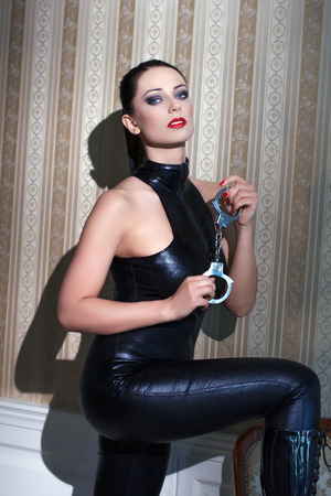 Sexy young woman in latex catsuit holding handcuffs photo