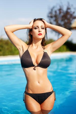 big boobs: Mujer atractiva con el pelo mojado y bikini posando en el agua, piscina Foto de archivo
