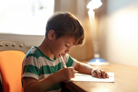bambini pensierosi: Ragazzino in scrittura a carta bianca sulla scrivania