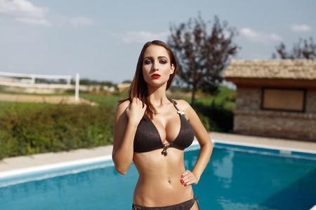 tetas: Mujer morena sexy en bikini posando en la piscina