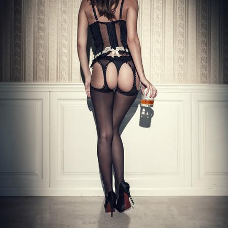 sexuales: Mujer atractiva con el culo bien formado y piernas largas que sostienen vaso de whisky. Estilo vintage