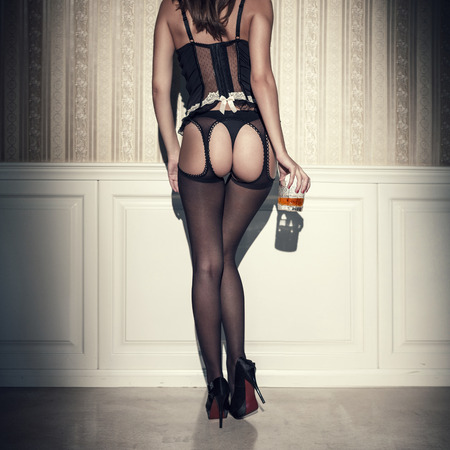 Sexy woman with well shaped ass and long legs holding glass of whiskey. Vintage style Stock Photo