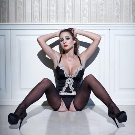 mujer desnuda sentada: Mujer atractiva en ropa interior se sienta en el piso, la sensualidad