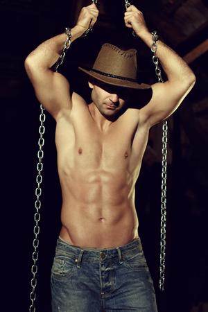 33872292-hombre-atractivo-en-sombrero-de-vaquero-con-la-cadena-en-el-granero.jpg?ver=6